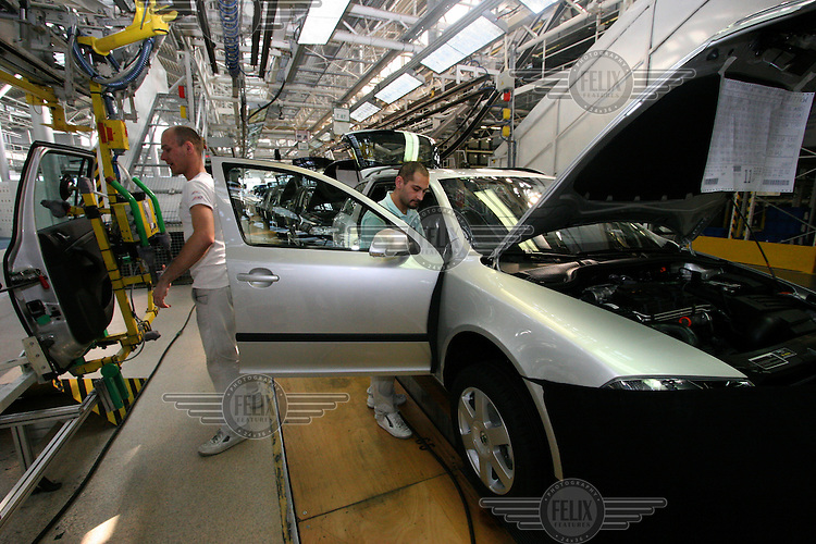 Workers install car doors to the body frame of Octavia vehicles on the assembly line at the Skoda car factory in Mlada Boleslav. Czech car producer Skoda Auto is a subsidiary of the Volkswagen (VW) Group.