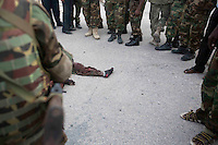 Members of AMISOM and Somali National Army stand over the dead bodies of al-Shabaab militants after the siege.