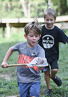 "Isaac Martin, 5, of Bentonville (from left) and brother Asher Martin, 7, react as he carries a handful of crawdads from a creek, Sunday, July 27, 2020 at Coler Mountain Bike Preserve in Bentonville. Andrew Martin moved his family to Northwest Arkansas from Dallas in January and with the plan of taking advantage of the area's outdoor sights. ""It's way better to be quarantined here where you can get outside and do stuff like this than be in the city,"" he said. Check out nwaonline.com/200728Daily/ for today's photo gallery. <br /> (NWA Democrat-Gazette/Charlie Kaijo)"