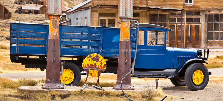 Shell Gasoline pumps outside the Boone Store and Warehouse with the Wheaton and Hollis Hotel in the background. One of fewer than 170 structures remaining in the ghost town of Bodie; gold discovered here in 1859. Designated National Historic Landmark in 1961; 1962 it became Bodie State Historic Park. Bodie named California's official state gold rush ghost town. Historic District, California State Park. Mono County, CA.