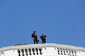 Members of the Secret Service Uniformed Division located on the roof of the White House watch over the 2015 Easter Egg Roll on the South Lawn of the White House, in Washington, DC on April 06, 2015.  The event features live music, sports courts, cooking stations, storytelling and Easter Egg Rolling. <br /> Credit: Aude Guerrucci / Pool via CNP