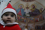 A Palestinian Christian boy takes part in the Christmas service during Christmas eve mass at a Catholic church in Gaza City, on December 24, 2010, a Christians around the world celebrate the birth of Jesus Christ. Photo by Mohammed Asad