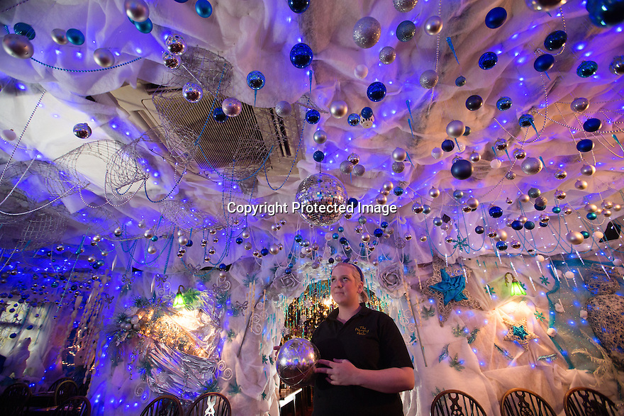 """30/11/15<br /> <br /> Manageress, Lisa Pearson, 27, puts up the final baubles in the 'Indoor Igloo'.<br /> <br /> It has taken a team of five, two weeks to put up this stunning display of Christmas decorations in what is believed to be one of Britain's most festive pubs. The race was on to put up the 7,500 baubles and 27,000 fairy lights, before guests arrived for the pub's first Christmas parties held last night. <br /> <br /> Each of the five rooms at the Hanging Gate at Chapel-en-le-Frith in the Derbyshire Peak District has a different theme or colour. This year the main restaurant is the Indoor Igloo, the bar area is purple and gold and there's the Candy Cain room upstairs in the pub near Buxton. There's also has another 10,000 lights on the outside of the building. <br /> <br /> """"We've had to replace a few thousand of the LED lights this year, I buy them in huge lengths so it's cost lots  to get everything ready"""" said landlord Mark Thomas.<br /> <br /> All Rights Reserved: F Stop Press Ltd. +44(0)1335 418365   www.fstoppress.com."""
