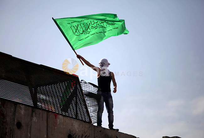 A Palestinian protester waves Hamas movement flag during clashes with Israeli security forces following a protest against Israel's restrictions at the Al-Aqsa Mosque in Jerusalem, at the Israeli Qalandia checkpoint between the West Bank city of Ramallah and Jerusalem, November 14, 2014. Israel eased restrictions at Jerusalem's Al-Aqsa mosque after US Secretary of State John Kerry announced agreement on steps to reduce tensions at the flashpoint compound. Photo by Shadi Hatem