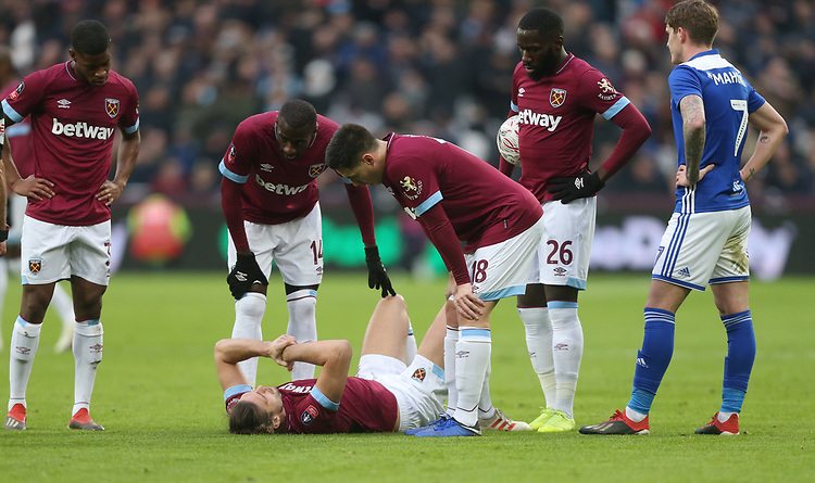 West Ham United's Xande Silva, Samir Nasri, Arthur Masuaku and Pedro Obiang look over the injured Andy Carroll<br /> <br /> Photographer Rob Newell/CameraSport<br /> <br /> Emirates FA Cup Third Round - West Ham United v Birmingham City - Saturday 5th January 2019 - London Stadium - London<br />  <br /> World Copyright &copy; 2019 CameraSport. All rights reserved. 43 Linden Ave. Countesthorpe. Leicester. England. LE8 5PG - Tel: +44 (0) 116 277 4147 - admin@camerasport.com - www.camerasport.com