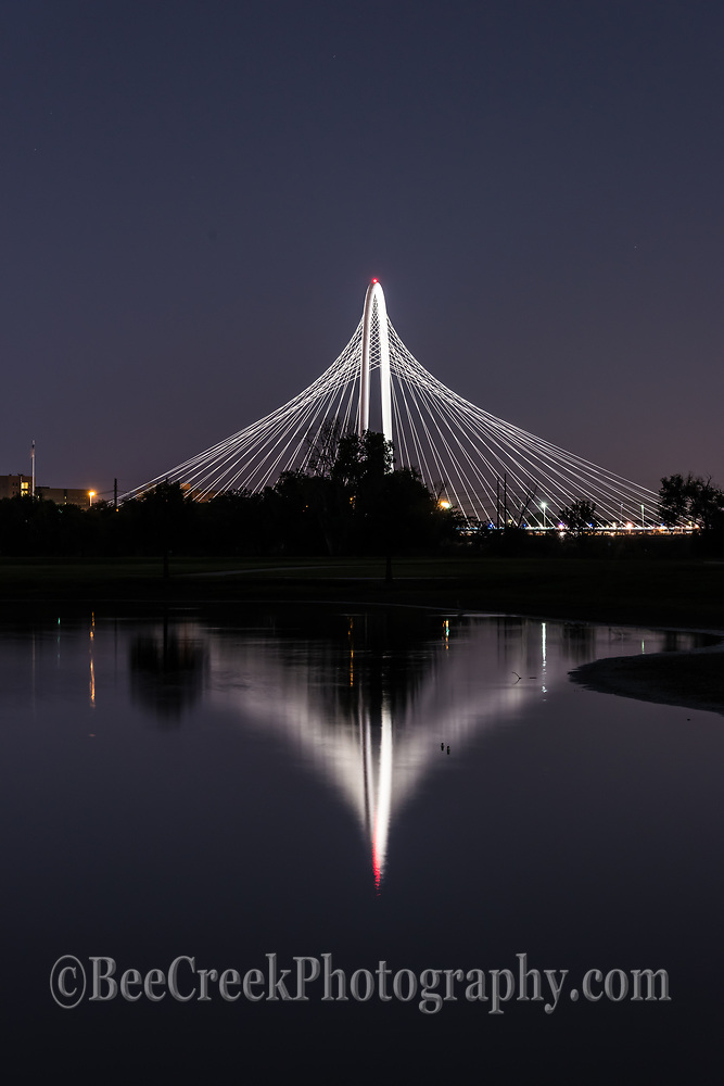 A vertical view of the Margaret Hunt Hill Bridge at night with it reflection in the waters of the Trinity River in downtown Dallas.