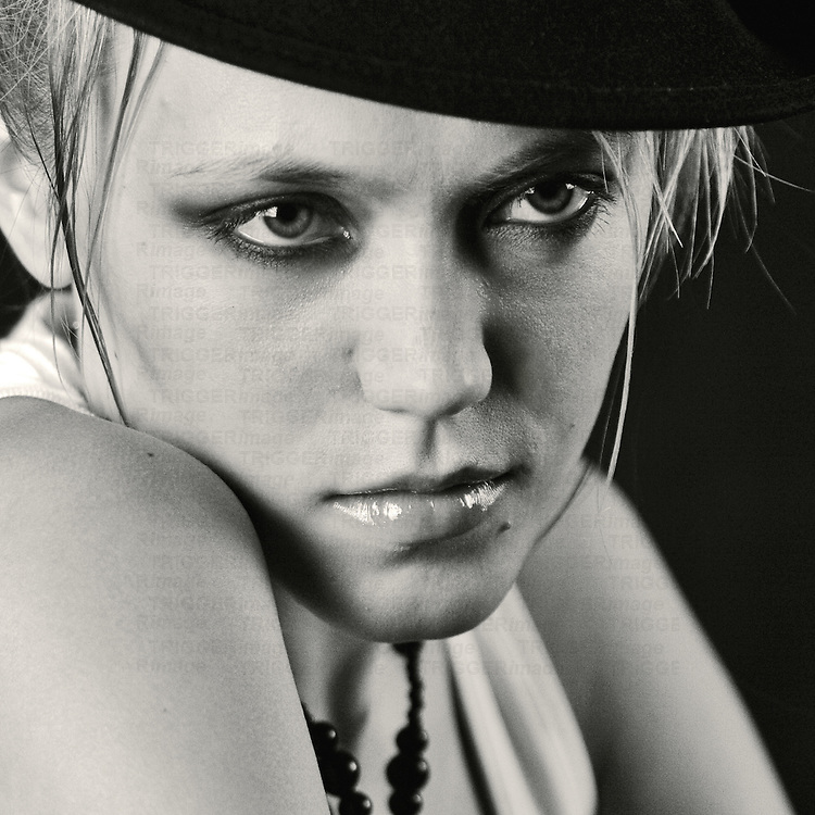 The face of a young woman wearing a black hat