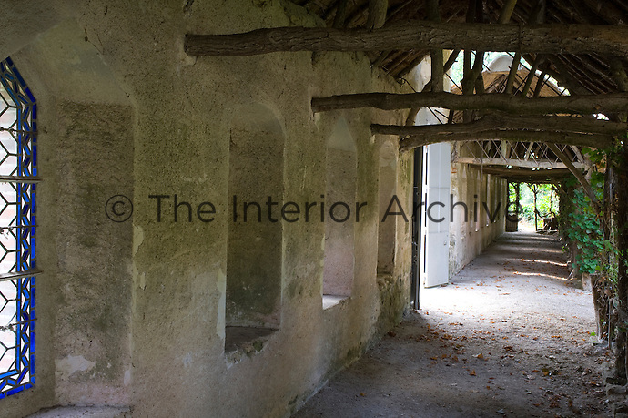 A covered walkway constructed of rough wooden beams leads to the gravelled courtyard garden