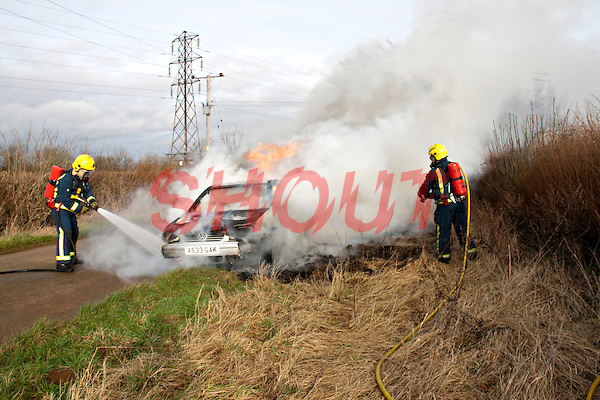 An abandoned car set alight being extinguished by firefighters wearing BA Oxfordshire UK. This image may only be used to portray the subject in a positive manner..©shoutpictures.com..john@shoutpictures.com