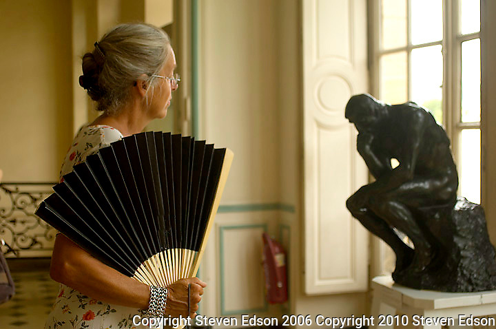 Lady with a fan viewing the Rodin statue, The Thinker
