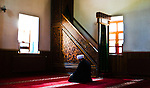 Imam praying in front of a window in Shamseddine türbesi in Konya, Turkey.