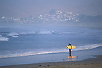 Surfer walking on sandy ocean beach looking at waves from Coleman Park, Morro Bay, California