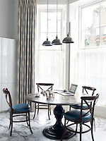 A pedestal table serves as a breakfast area in the bay window of the contemporary kitchen
