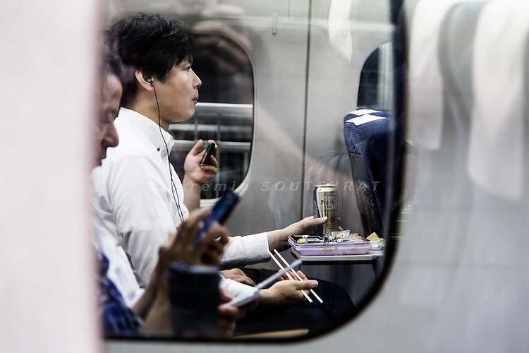 Tokyo, September 6 2013 - Salaryman eating a bento and drinking beer on the train.