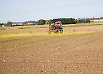 Farm machinery spraying Glyphosate herbicide on an arable field near Hollesley, Suffolk, England