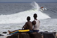 "Jon Rose surfs the wave called ""Cottontrees"" in Robertsport, Liberia, while local children look on."