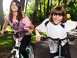 Two happy smiling children riding bicycles in a park, brother and sister, 10 and 13. Active outdoor lifestyle.
