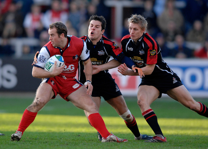 Photo: Richard Lane..Gloucester Rugby v Edinburgh Rugby. Heineken Cup. 09/12/2006. .Gloucester's James Simpson-Daniel is tackled by Edinburgh's Hugo Southwell and Ben Cairns.