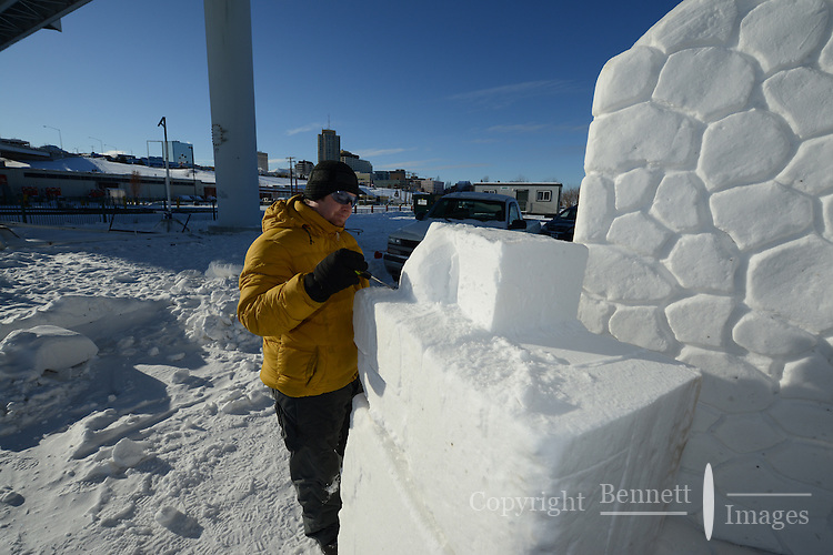 Wade Pier takes advantage of the bright winter sun to begin work on his snow sculpture, one of the premier events of the Anchorage, Alaska, Fur Rendezvous winter carnival in February, 2013.