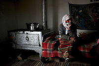 BULGARIA, Lazhnitsa, April 17, 2011. An elderly Bulgarian muslim woman sits next to a stove in her house in the remote village of Lazhnitsa in the Rhodope Mountains, southern Bulgaria. Bulgarian Muslims, which today are nearly 8% of the country's population and the largest muslim minority community in the European Union, revived their cultural and religious traditions after the fall of communist regime in Bulgaria in 1989. .BULGARIE, Lazhnitsa, 17 Avril 2011. Une Bulgare âgée de confession musulmane est assise près d'un poêle dans sa maison du petit village de Lazhnitsa dans les montagnes des Rhodopes en Bulgarie. La minorité musulmane qui représente aujourd'hui près de 8% de la population totale du pays et qui est la plus large majorité musulmane dans les pays de l'Union Européenne a ravive ses traditions culturelles et religieuse après la chute du régime communiste Bulgare en 1989.