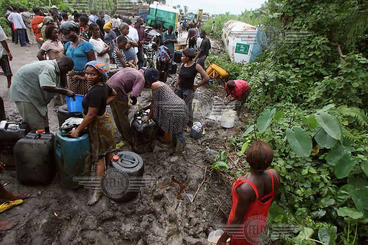 Locals take oil from an overturned oil tanker in the Niger Delta.