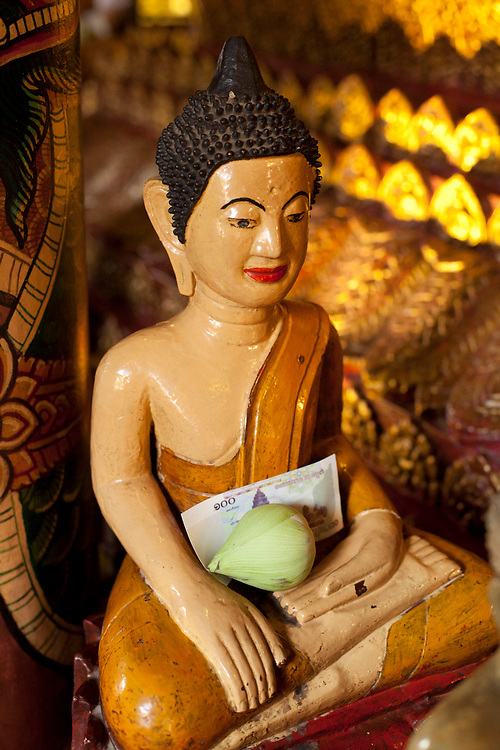 Buddha statue with offerings at Wat Phnom temple Phnom Penh, Cambodia. <br /> <br /> Photos &copy; Dennis Drenner 2013.