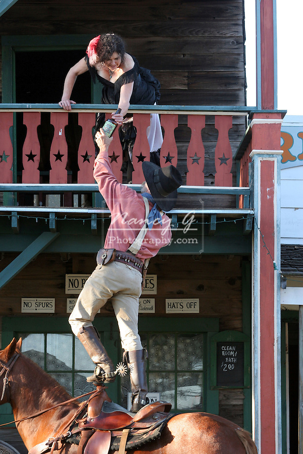 A cowboy sharing his bottle of alcohol with a young lady of the saloon hanging over the balcony