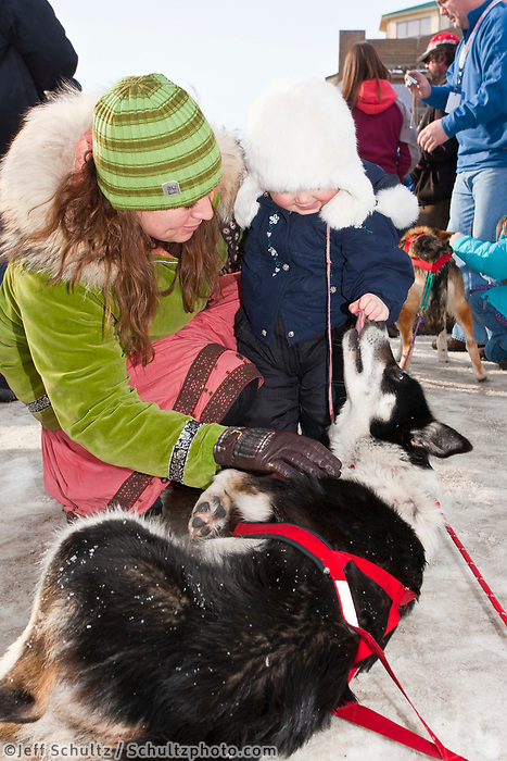 Race fans pet Jane Faulkner's dog Sharpie in the Nome finish chute during the 2010 Iditarod