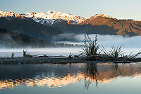 Sunrise over Southern Alps and Mount Tasman reflecting in Lake Mapourika near Franz Josef Glacier on winter morning, Westland Tai Poutini National Park, West Coast, UNESCO World Heritage Area, New Zealand, NZ