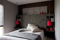 A small double bed benefits from a built-in headboard and side tables for lamps