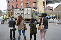 """Banksy enthusiasts flock to the trendy Meatpacking District in New York on Friday, October 11, 2013 to see the eleventh installment of Banksy's art, """"The Sirens of the Lambs"""". This particular sculptural piece consists of a slaughterhouse truck filled with bleating plush animals, controlled by puppeteers, which were driven around by a driver, who remained in character. The elusive street artist is creating works around the city each day, during the month of October accompanied by a satirical recorded message parodying a museum tour which you can get by calling the number 1-800-656-4271 followed by  # and the number of artwork.  (© Richard B. Levine)"""