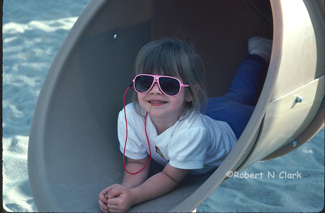 Girl in tube slide at park, wearing sunglasses
