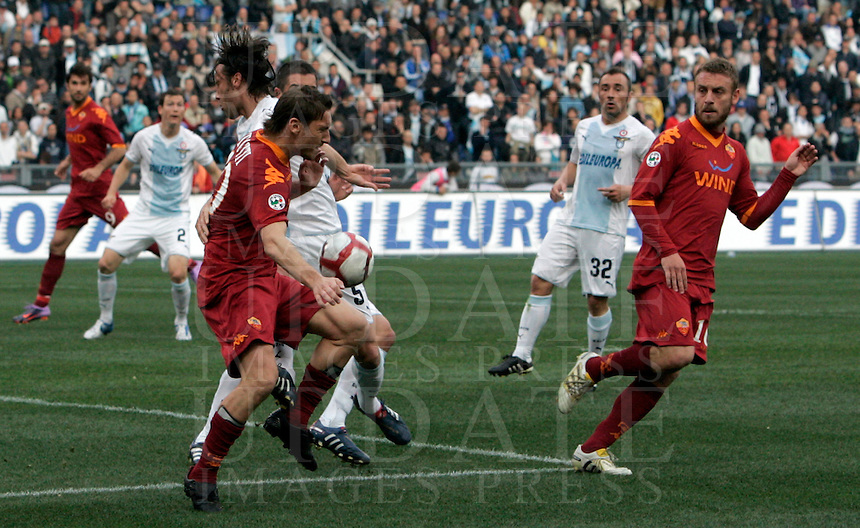 Calcio, Serie A: Lazio-Roma. Roma, stadio Olimpico, 18 aprile 2010..Football, Italian serie A: Lazio-Roma. Rome, Olympic stadium, 18 aprile 2010. AS Roma forward Francesco Totti, left, in red, fights for the ball with Lazio midfielder Stefano Mauri, as AS Roma midfielder Daniele De Rossi, right, and Lazio midfielder Cristian Brocchi, second from left, look on..UPDATE IMAGES PRESS/Riccardo De Luca