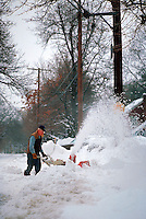 Man using a snowblower to clear away snow.