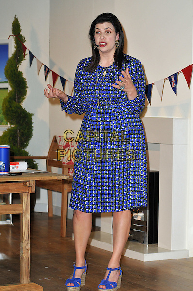 Kirstie Allsopp workshop at the B&Q How to Theatre, Ideal Home Show, Earls Court Exhibition Centre, London, UK. The property guru hosts workshop to encourage visitors to be more creative when styling their home. She shares ideas for the Diamond Jubilee and demonstrates how to make bunting..March 28th, 2012.full length dress blue print  hands arms mouth open.CAP/BF.©Bob Fidgeon/Capital Pictures.