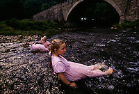 Sunday church dresses double as bathing suits for the Byler sisters below the Casselman River Bridge. Now closed to all but foot traffic, the bridge was built in 1813 like a lone cathedral rib. The 50-foot arch was designed to clear a canal that never came