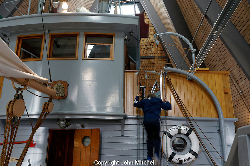 Boy climbing ladder on the RCMP St. Roch schooner, Vancouver Maritime Museum, Vancouver, BC, Canada