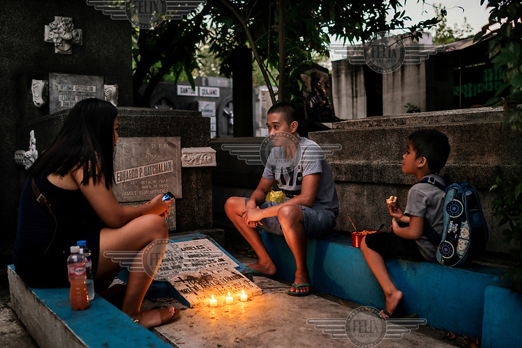 Visitors pay their respects and pray at a family tomb at Manila North Cemetery.  Manila North Cemetery is home to thousands of 'informal settlers' who have built shacks using in and around the mausoleums, crypts and tombs. In comparison to the city's dangerous shantytowns the cemetery is relatively quiet and safe. However, water must be collected from a few public wells and the electricity supply is erratic, usually stolen from mains cables. In the summer the sweltering heat drives people to sleep outside often on top of the tombs.<br /> <br /> Some of the residents live in the crypts and mausoleums of wealthy families, who pay them a stipend to clean and watch over them. Others make a living carving headstones or selling candles to visitors and helping out at funerals as the daily life of the cemetery goes on around the people who live there.