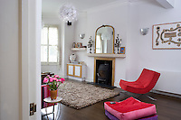 The living room has been furnished with an antique mirror and candelabra on the fireplace and an aboriginal artwork on the wall adjacent to a 1960's armchair