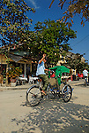 Asia, Vietnam, Hoi An. Hoi An old quarter. Waving cyclo driver. The historic buildings, attractive tube houses, and decorated community halls have 1999 earned Hoi An's old quarter the status of a UNESCO World Heritage Site. To protect the old quarter's character stringent conversation laws prohibit alterations to buildings, as well as the presence of cars on the roads.