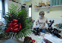 Florist Connie Bailey in Buckhannon, WV, makes black ribbon bows Friday, Jan. 6, 2006, to be displayed to honor the miners killed in a mine explosion Monday at a mine in Sago. Twelve miners died in the explosion. (Photo by Gary Gardiner)....<br />