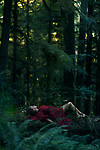 Young woman in red dress lying on a tree in a beautiful tranquill deep green mossy woods magical nature scenery