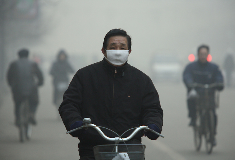 A man wears a mask as he rides a bike to work in the polluted town of Linfen.