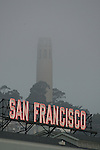 San Francisco's neon sign greets passengers getting off the fairies on the waterfront with Coit Tower in the background.