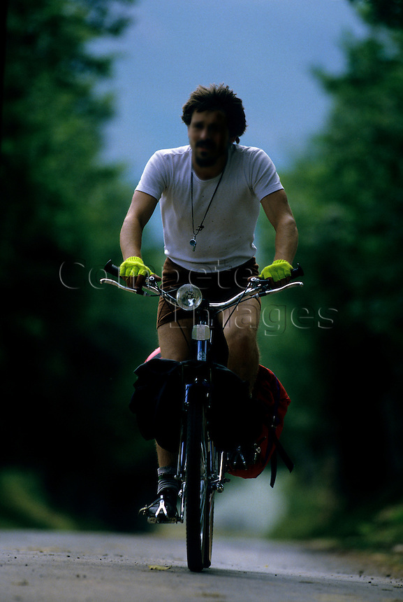 Man riding a bicycle up a country lane