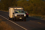 White Ford with lumber rack towing enclosed trailer