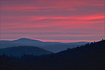 Just before sunrise, the sky over the North Quabbin valley fills with brilliant color as seen for the Route 202 overlook in New Salem, Massachusetts.  In the distance Mount Monadnock can be seen.