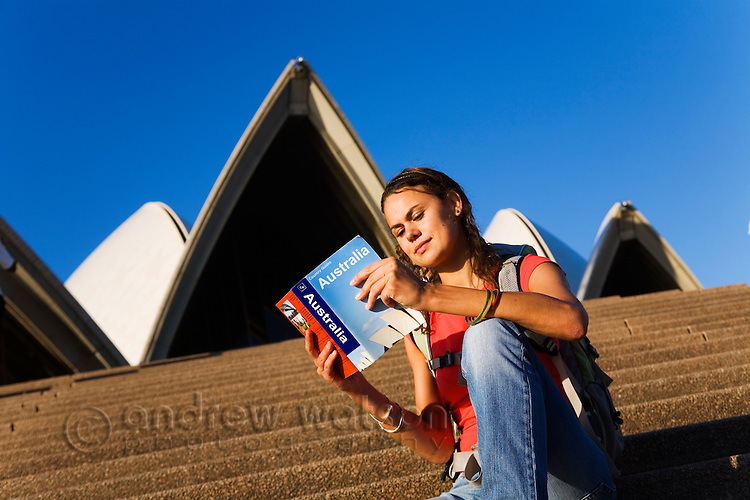 A woman reads her guidebook on the steps of the Sydney Opera House.  Sydney, New South Wales, AUSTRALIA.