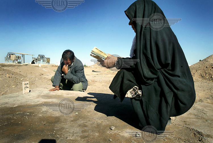 Parents grieving over their daughters, killed in the Bam earthquake and buried in a mass grave..An earthquake measuring 6.3 on the Richter scale caused widespread devastation in the ancient city of Bam and other parts of Kerman Province, leaving at least 30,000 people dead.