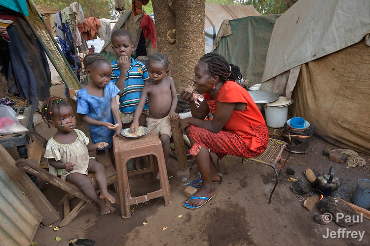 A mother and her children eat a meal in a camp for more than 12,000 internally displaced persons located on the grounds of the Roman Catholic Cathedral of St. Mary in Wau, South Sudan. Most of the families here were displaced in June, 2016, when armed conflict engulfed Wau.<br /> <br /> Norwegian Church Aid, a member of the ACT Alliance, has provided relief supplies to the displaced in Wau, and has supported the South Sudan Council of Churches as it has struggled to mediate the conflict in Wau.